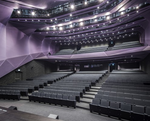 The use of gradation in colour, receding wall and ceiling modules in the Auditorium enhances its directional quality in an otherwise fairly static space
