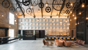 A double-volume space greets visitors at the Hotel lobby, complete with the original warehouse trusses.